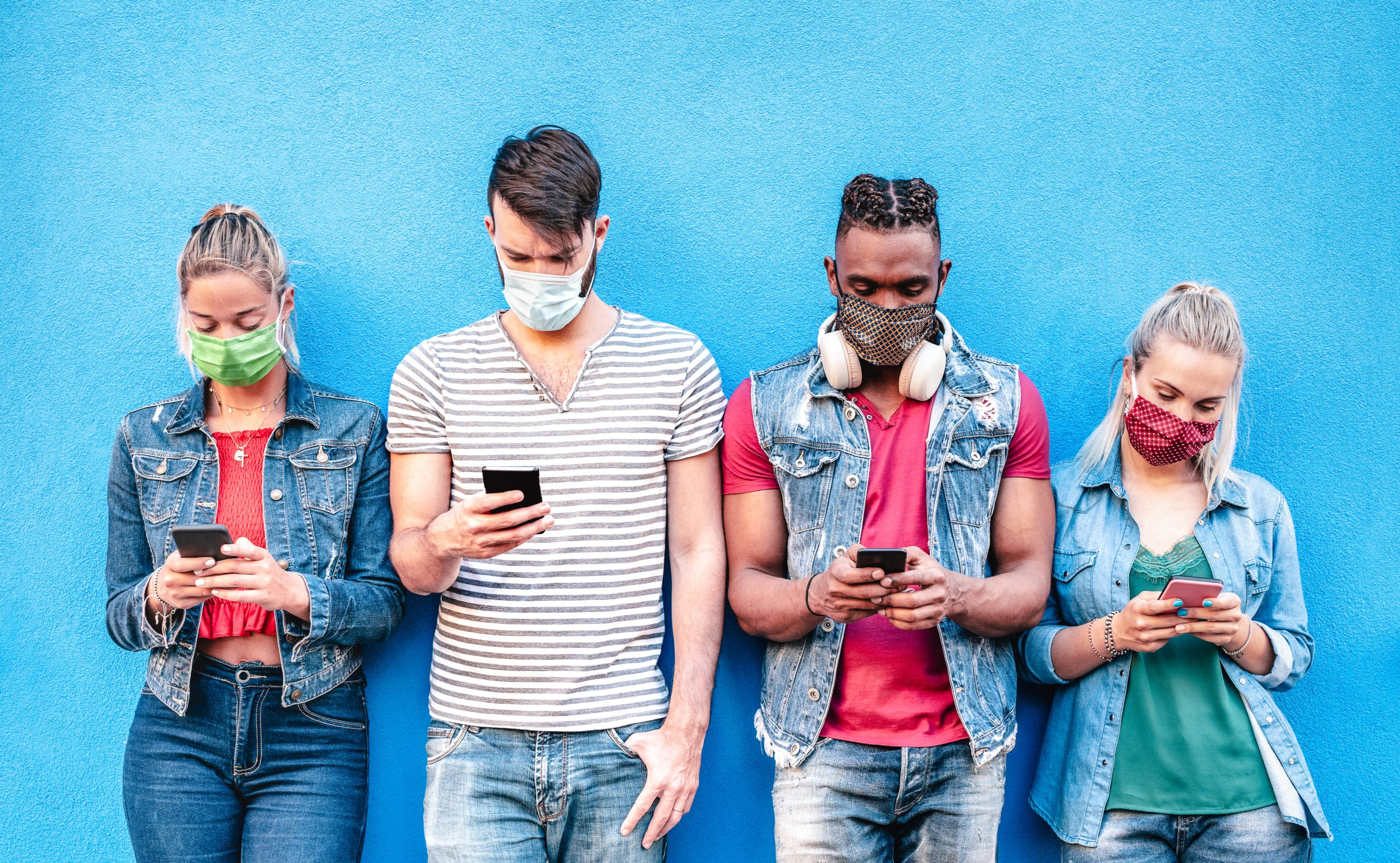 Gen Z people engaging with a Mobilize community on their phones in masks